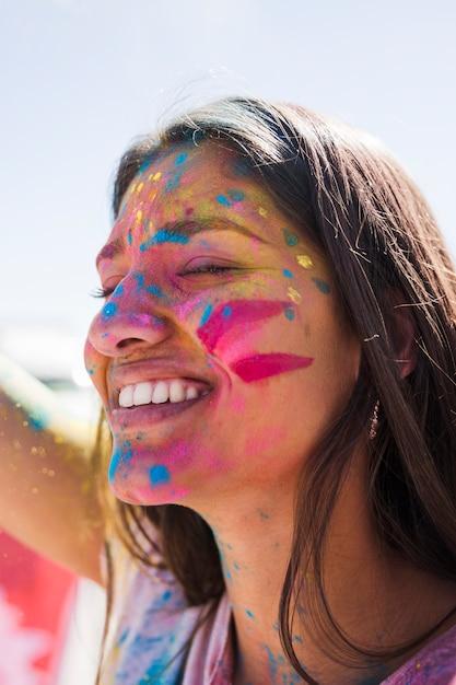 Holi couleur sur le visage de la femme souriante Photo gratuit
