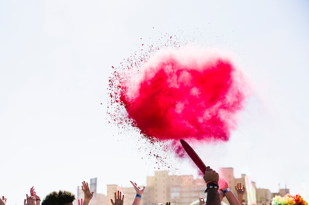 Holi rouge explosion de couleurs sur la foule Photo gratuit