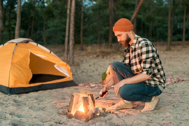 Homme accroupi commençant un feu de joie Photo gratuit