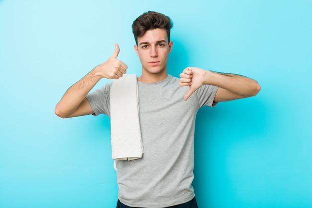 Homme adolescent adolescent de remise en forme montrant les pouces vers le haut et vers le bas, difficile choisir le concept Photo Premium
