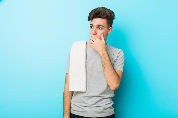 Homme adolescent adolescent de remise en forme réfléchie à la recherche d'un espace copie couvrant la bouche avec la main. Photo Premium