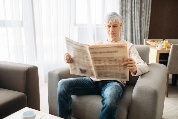 Homme Adulte Assis Sur Le Canapé Et Lisant Le Journal à La Maison