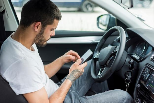 Homme adulte assis dans la voiture et à l'aide de smartphone Photo gratuit