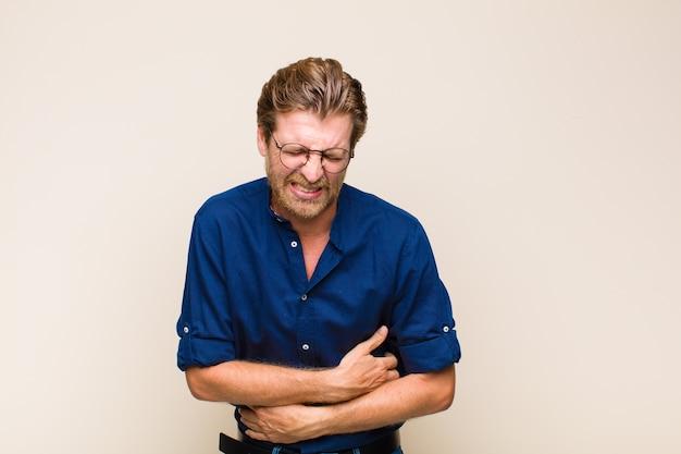 Homme Adulte Blond Se Sentant Anxieux, Malade, Malade Et Malheureux, Souffrant De Maux D'estomac Ou De Grippe Douloureux Photo Premium