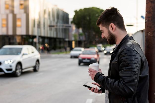 Homme adulte avec café à l'aide d'un téléphone portable Photo gratuit