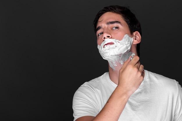 Homme adulte confiant se raser la barbe Photo gratuit