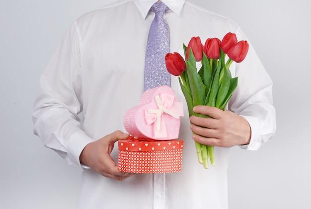 Homme Adulte Dans Une Chemise Blanche Et Une Cravate Lilas Tenant Un Bouquet De Tulipes Rouges Avec Des Feuilles Vertes Et Coffret Cadeau Photo Premium