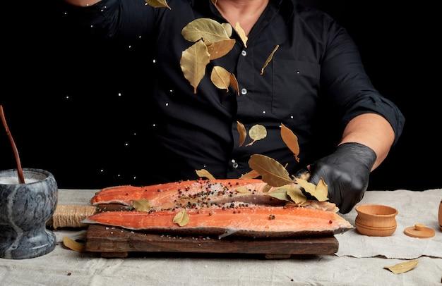 Homme Adulte Dans Une Chemise Noire Verse Du Gros Sel Blanc Et Une Feuille De Laurier Sèche Sur Un Filet De Saumon Frais Photo Premium