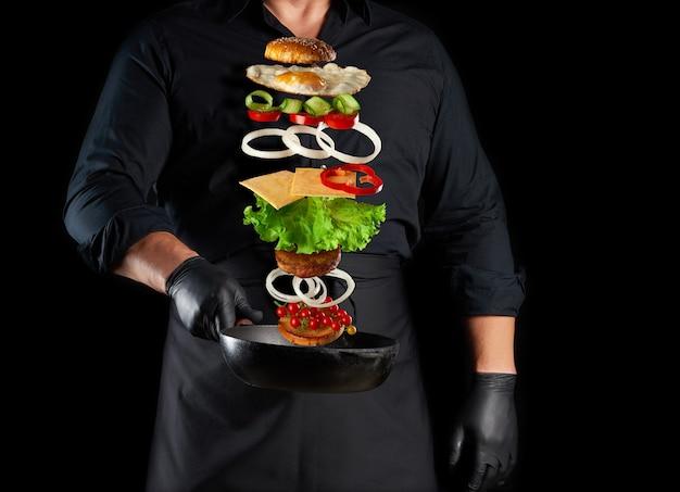 Homme Adulte Dans Un Uniforme Noir Tenant Une Poêle Ronde En Fonte Avec Des Ingrédients Cheeseburger En Lévitation Photo Premium