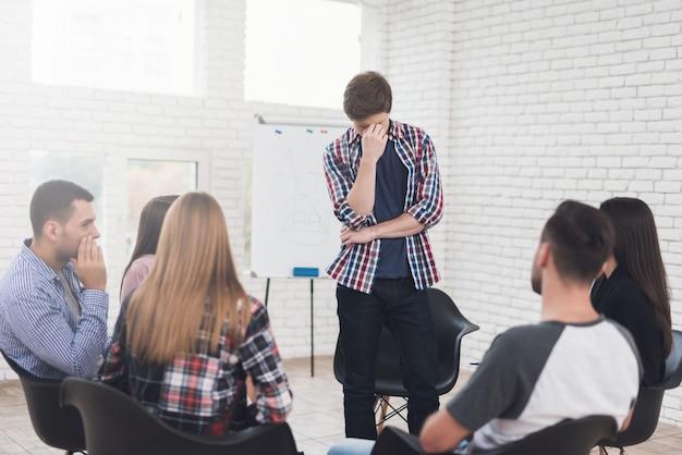 Homme adulte se tient en cercle de personnes au cours de la thérapie de groupe. Photo Premium