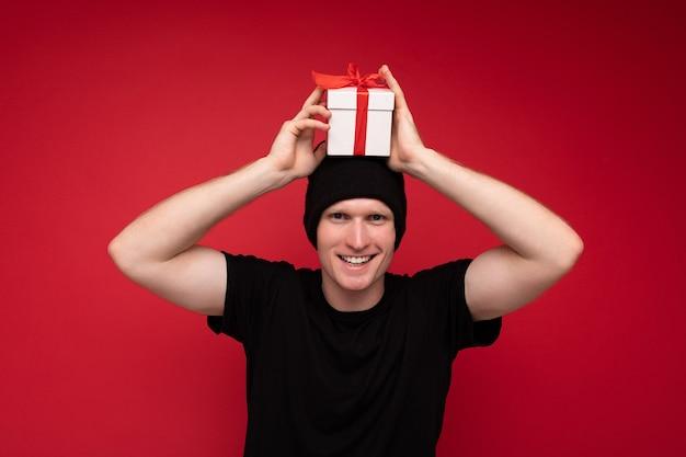 Homme Adulte Souriant Isolé Sur Le Mur De Fond Rouge Portant Un Chapeau Noir Et Un T-shirt Noir Tenant Une Boîte Cadeau Blanche Avec Un Ruban Rouge Et Regardant La Caméra Et S'amuser. Photo Premium