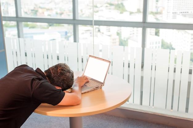 Homme d'affaire. faire une sieste, fatigué du travail, dormir devant un ordinateur portable, allongé sur ses mains. Photo Premium