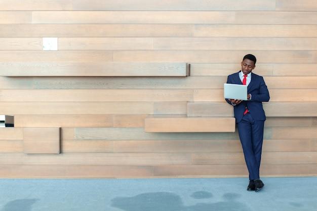 Homme d'affaires africain intelligent à l'aide d'un ordinateur portable au bureau avec fond Photo Premium