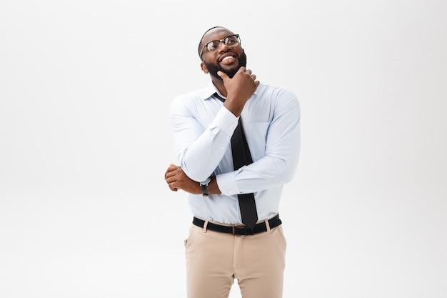 Homme d'affaires afro-américain avec des lunettes pense sur fond blanc isolé Photo Premium