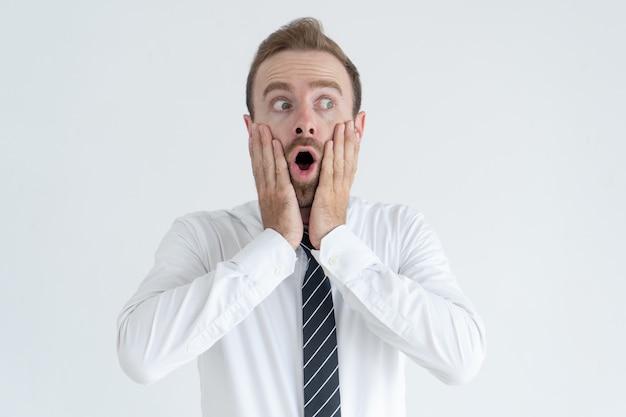 Homme d'affaires d'âge moyen choqué touchant les joues et regardant loin avec sa bouche ouverte Photo gratuit