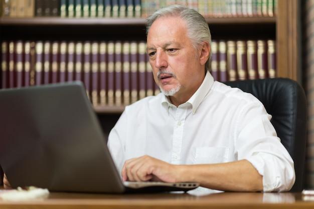 Homme d'affaires à l'aide de son ordinateur portable dans une bibliothèque Photo Premium