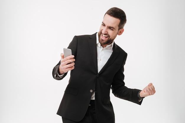 Homme D'affaires à L'aide De Téléphone Portable Et Faites Le Geste Du Gagnant. Photo Premium