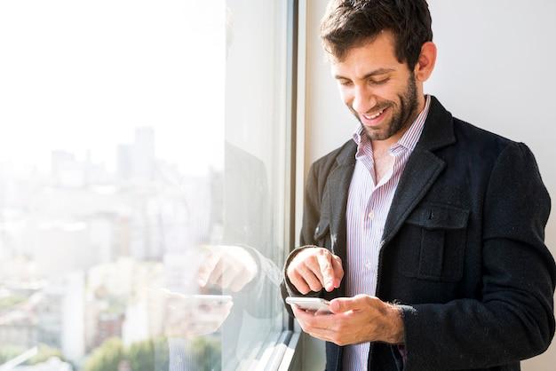Homme d'affaires à l'aide d'un téléphone portable Photo gratuit