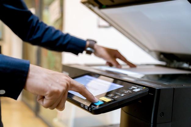 Homme d'affaires appuyez à la main sur le panneau de l'imprimante. Photo Premium