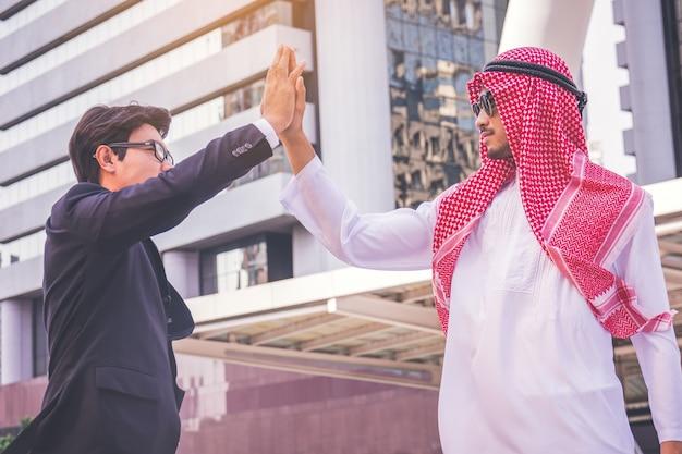 Homme d'affaires arabe donnant un haut cinq à son partenaire, sur un chantier de construction Photo Premium
