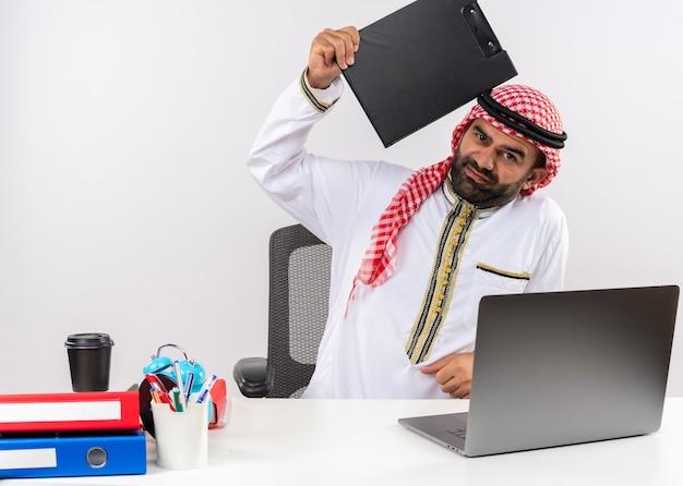 Homme D'affaires Arabe Mécontent En Vêtements Traditionnels Assis à La Table Avec Un Ordinateur Portable Tenant Le Presse-papiers Avec Des émotions Négatives Travaillant Au Bureau Photo gratuit