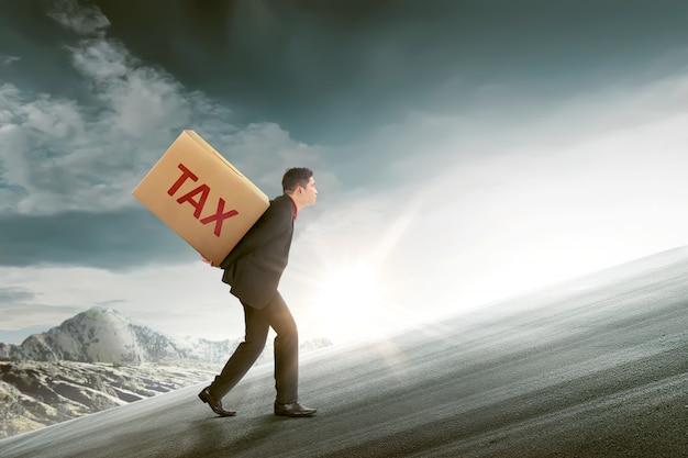 Homme d'affaires asiatique attrayant apporter le carton de la taxe Photo Premium
