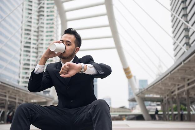 Homme d'affaires asiatique beau boire du café chaud et regarder la montre-bracelet pour vérifier l'heure Photo Premium