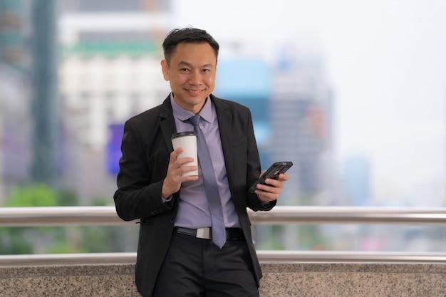 Homme d'affaires asiatique debout et tenant un téléphone portable avec des immeubles de bureaux dans la ville Photo Premium
