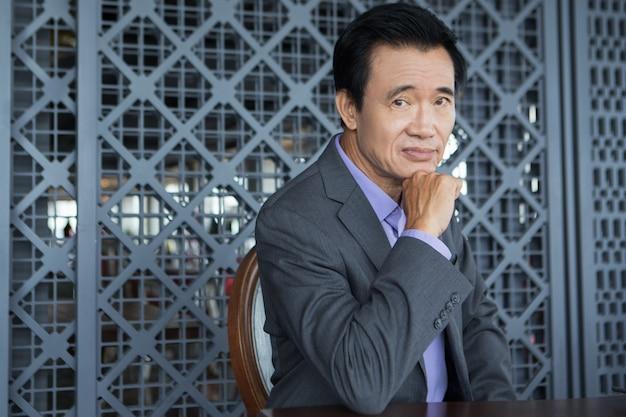 Homme d'affaires asiatique fatigué assis restaurant Photo gratuit