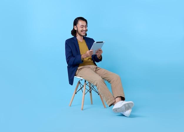 Homme D'affaires Asiatique Heureux Souriant à L'aide D'une Tablette Numérique Alors Qu'il était Assis Sur Une Chaise Bleu Vif. Photo gratuit