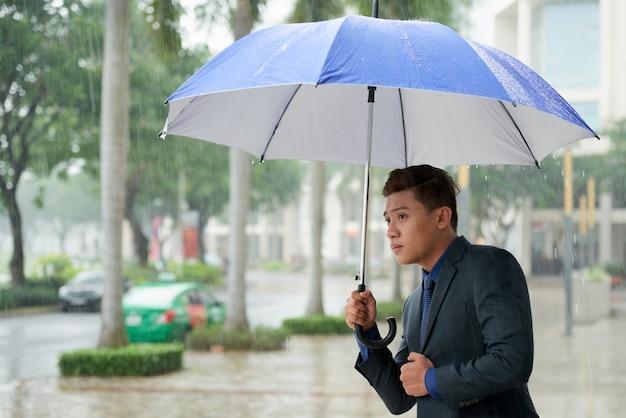 Homme d'affaires asiatique avec parapluie à la recherche d'un taxi dans la rue pendant la pluie Photo gratuit
