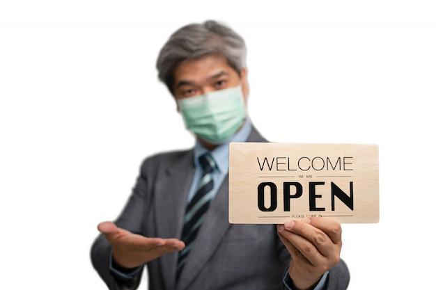 Homme D'affaires Asiatique Porter Des Masques Médicaux Sur Le Fond Isolé Et Tenant Bienvenue, Nous Sommes Signe Ouvert Photo Premium