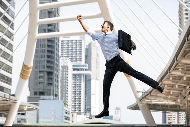 Homme d'affaires asiatique, sautant avec un bras levé en geste de réussite Photo Premium