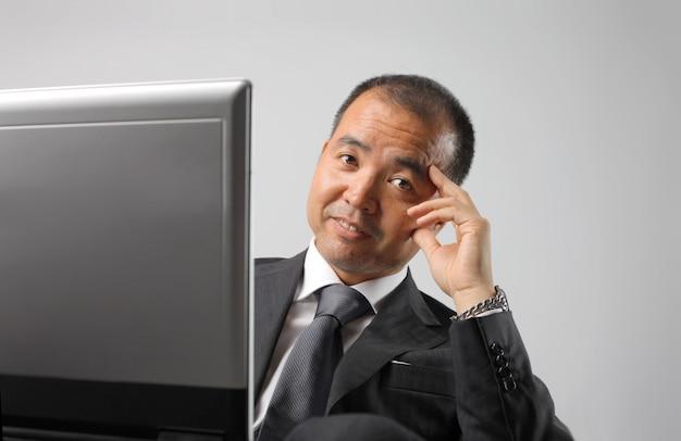 Homme d'affaires asiatique avec son ordinateur Photo Premium