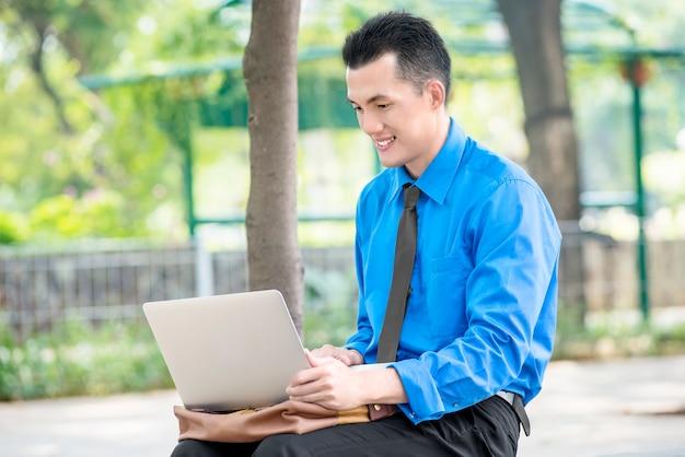 Homme d'affaires asiatique souriant assis et travaillant avec un ordinateur portable Photo Premium