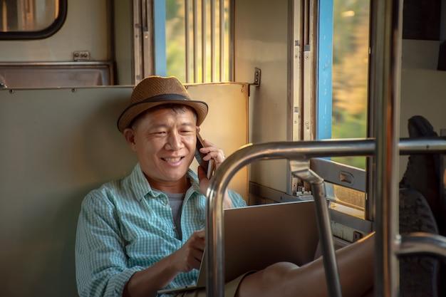 Homme d'affaires asiatique travaillant en ligne avec un ordinateur portable et un téléphone portable se sentent détendus lors d'un voyage en train Photo Premium