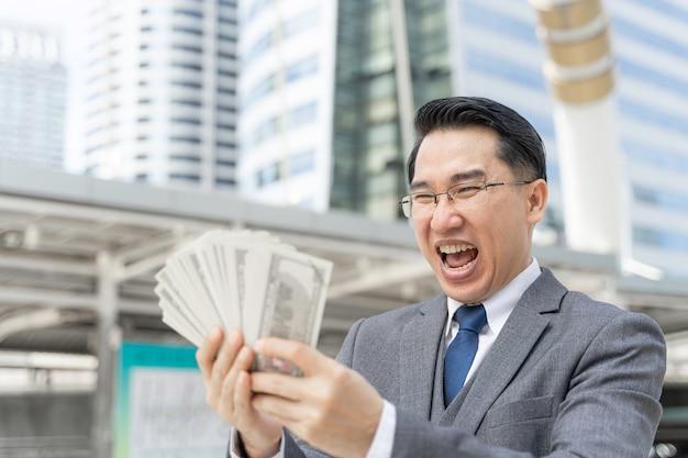 Homme D'affaires Asiatique Visage Heureux Détenant Des Billets D'un Dollar Américain Sur Le Quartier Des Affaires Urbain Photo gratuit