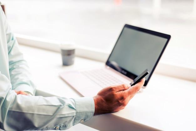 Homme d'affaires d'asie travaillant avec un ordinateur portable assis au café Photo Premium