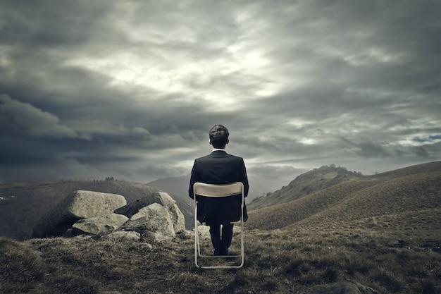 Homme D'affaires Assis Sur Une Chaise Sur La Montagne Photo Premium