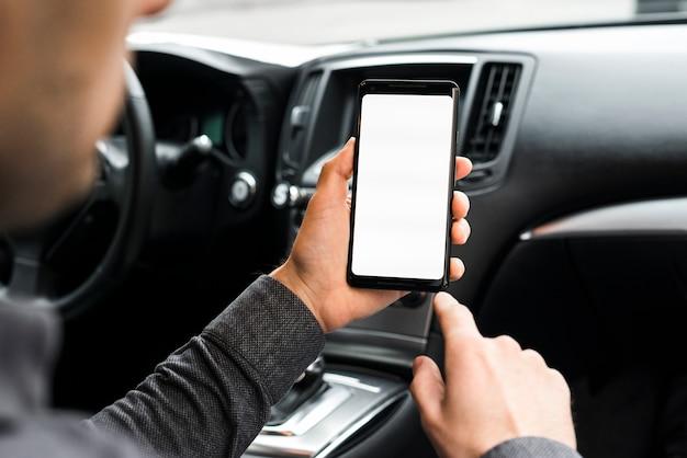Un homme d'affaires assis dans la voiture à l'aide de téléphone portable avec écran blanc Photo gratuit