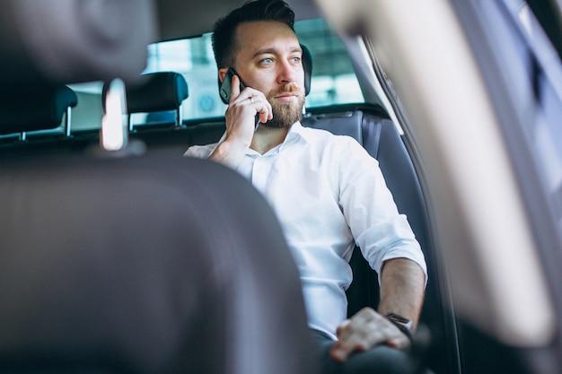 Homme d'affaires assis dans une voiture à l'aide de téléphone Photo gratuit