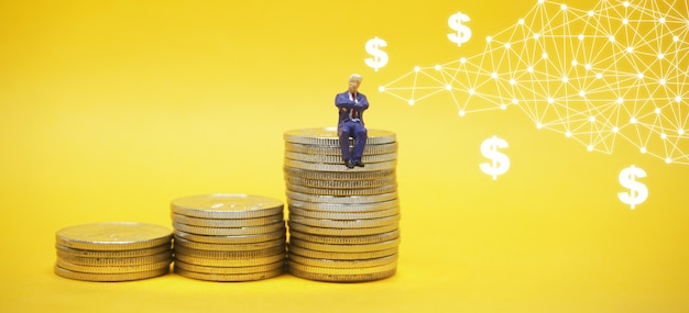 Homme d'affaires assis sur un tas de pièces Photo Premium