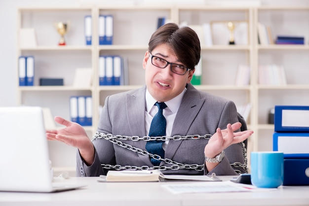 Homme d'affaires attaché avec des chaînes à son travail Photo Premium