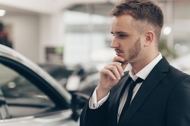 Homme d'affaires attrayant acheter une nouvelle voiture chez le concessionnaire Photo Premium