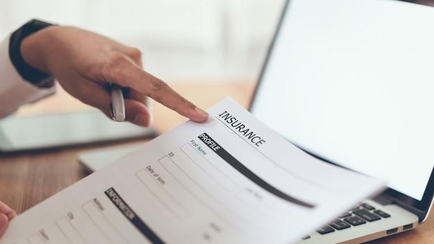 Homme d'affaires au bureau remplir une police d'assurance. pour éviter de futurs incidents. Photo Premium