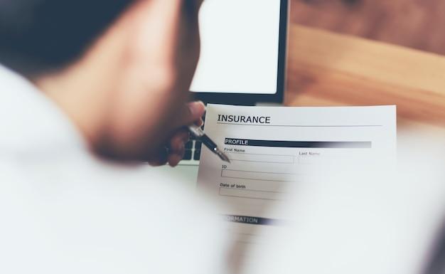 Homme d'affaires au bureau remplissent une police d'assurance. pour prévenir de futurs incidents. Photo Premium