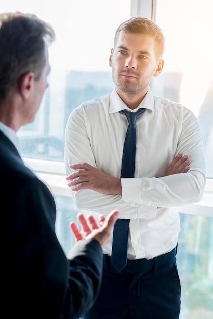 Homme d'affaires ayant une conversation avec son partenaire masculin au bureau Photo gratuit