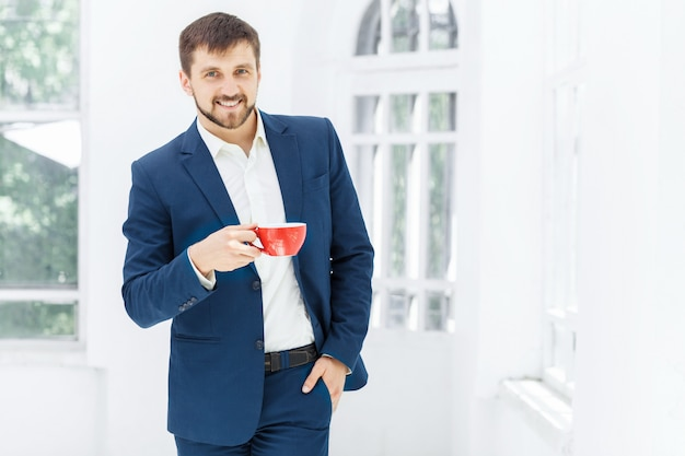Homme D'affaires Ayant Une Pause-café, Il Tient Une Tasse Photo gratuit