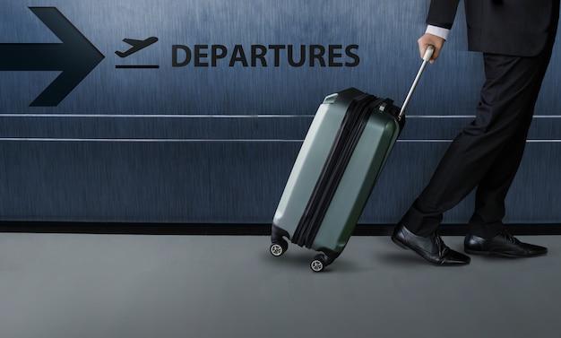 Homme d'affaires avec des bagages à pied à l'intérieur du terminal des départs de l'aéroport Photo Premium