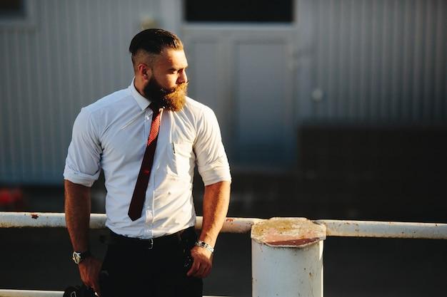 Homme d'affaires sur une balustrade blanche Photo gratuit
